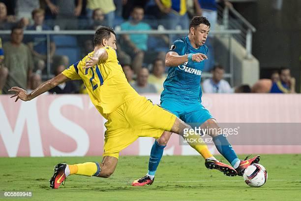 Zenit's midfielder Giuliano dribbles past Maccabi's defender Egor Filipenko during their UEFA Europa League Group D football match between Israel's...