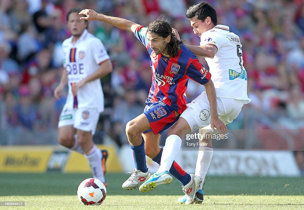 Zenon Caravella of the Jets contests the ball with Cameron Edwards of the Glory during the round two A-League match between the Newcastle Jets and the Perth Glory at Hunter Stadium on October 20, 2013 in Newcastle, Australia.