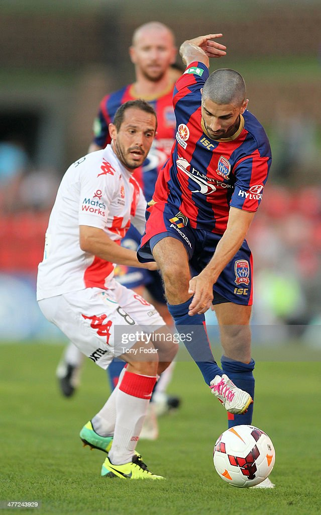 Zenon Caravella of the Jets contestst the ball against Massimo Murdocca of the Heart during the round 22 A-League match between the Newcastle Jets and Melbourne Heart at Hunter Stadium on March 8, 2014 in Newcastle, Australia.