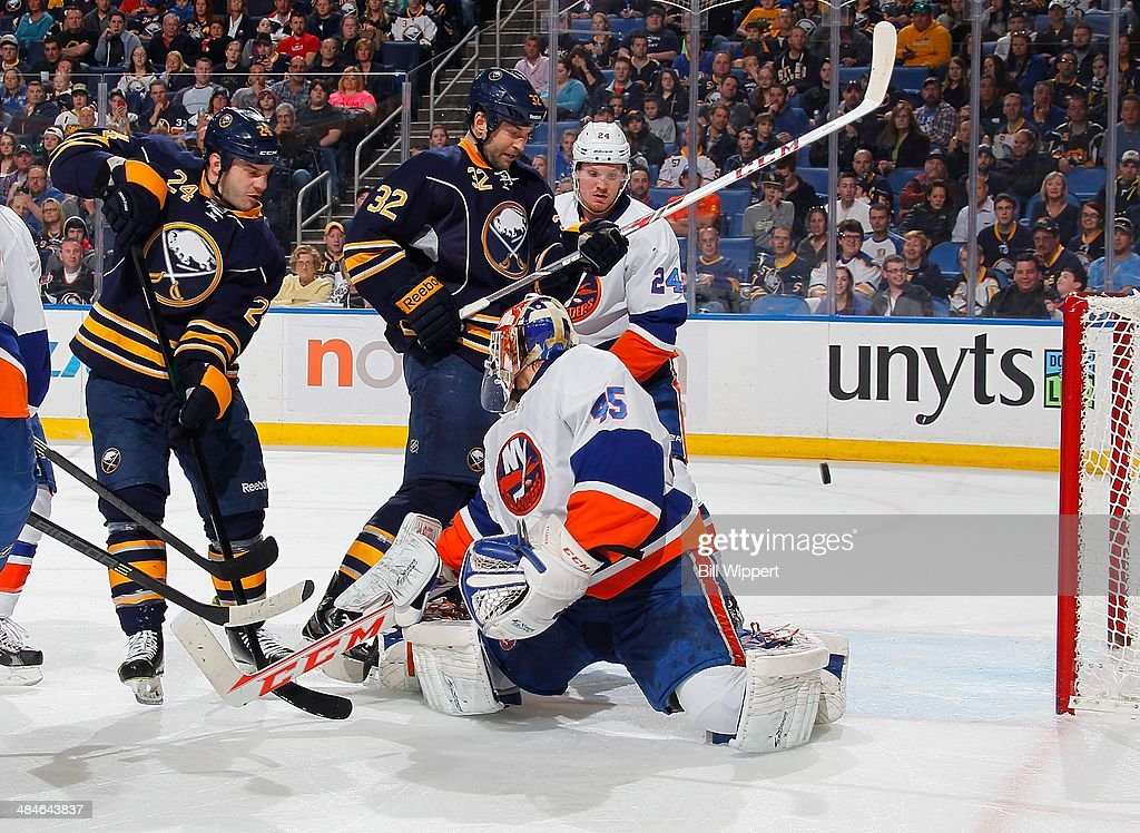 Zenon Konopka #24 and John Scott #32 of the Buffalo Sabres look to deflect a puck that goes past goaltender Anders Nilsson #45 of the New York Islanders on April 13, 2014 at the First Niagara Center in Buffalo, New York.