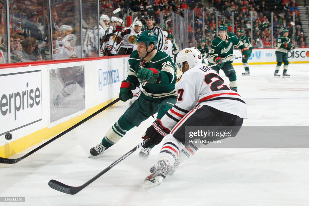 <a gi-track='captionPersonalityLinkClicked' href=/galleries/search?phrase=Zenon+Konopka&family=editorial&specificpeople=2105876 ng-click='$event.stopPropagation()'>Zenon Konopka</a> #28 of the Minnesota Wild controls the puck while <a gi-track='captionPersonalityLinkClicked' href=/galleries/search?phrase=Johnny+Oduya&family=editorial&specificpeople=3944055 ng-click='$event.stopPropagation()'>Johnny Oduya</a> #27 of the Chicago Blackhawks defends during the game on April 9, 2013 at the Xcel Energy Center in Saint Paul, Minnesota.