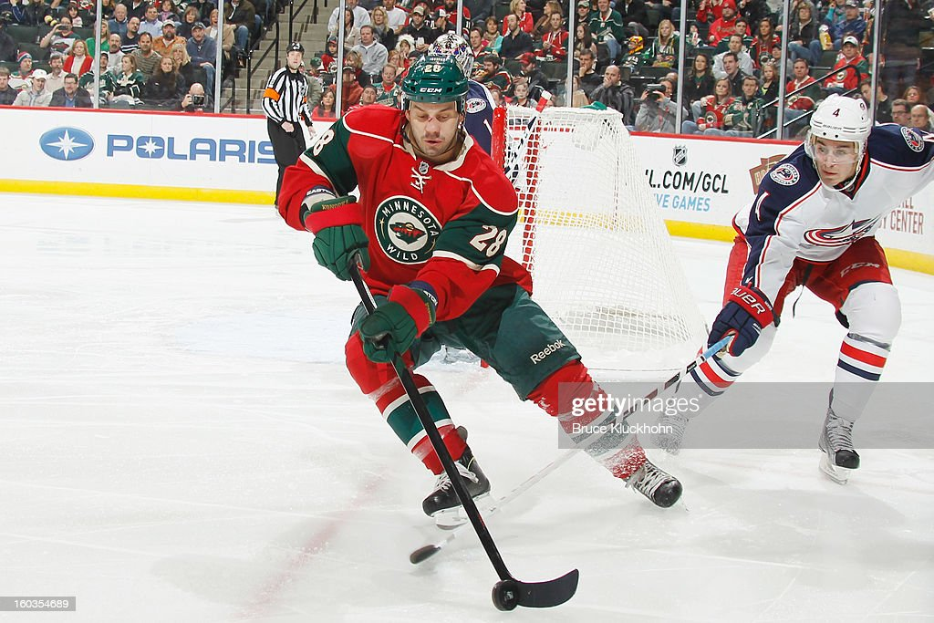 <a gi-track='captionPersonalityLinkClicked' href=/galleries/search?phrase=Zenon+Konopka&family=editorial&specificpeople=2105876 ng-click='$event.stopPropagation()'>Zenon Konopka</a> #28 of the Minnesota Wild skates with the puck while John Moore #4 of the Columbus Blue Jackets defends during the game on January 29, 2013 at the Xcel Energy Center in Saint Paul, Minnesota.