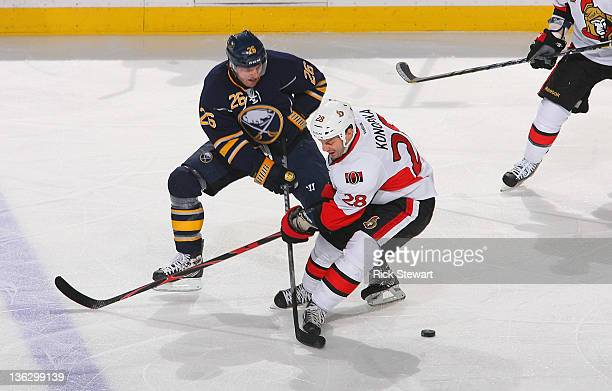 Zenon Konopka of the Ottawa Senators is poke checked by Thomas Vanek of the Buffalo Sabres at First Niagara Center on December 31 2011 in Buffalo New...