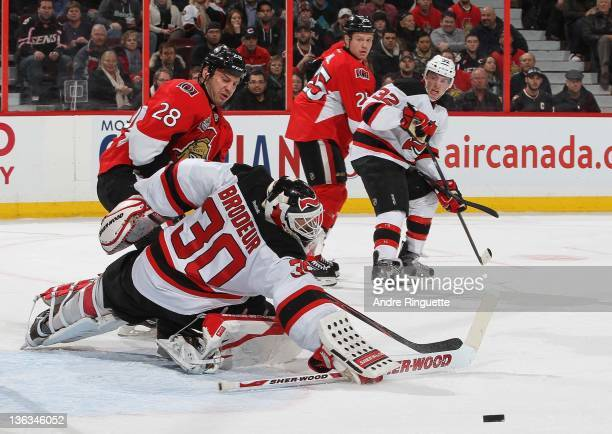 Zenon Konopka of the Ottawa Senators skates to the net looking for a rebound as Martin Brodeur of the New Jersey Devils makes a save with Chris Neil...