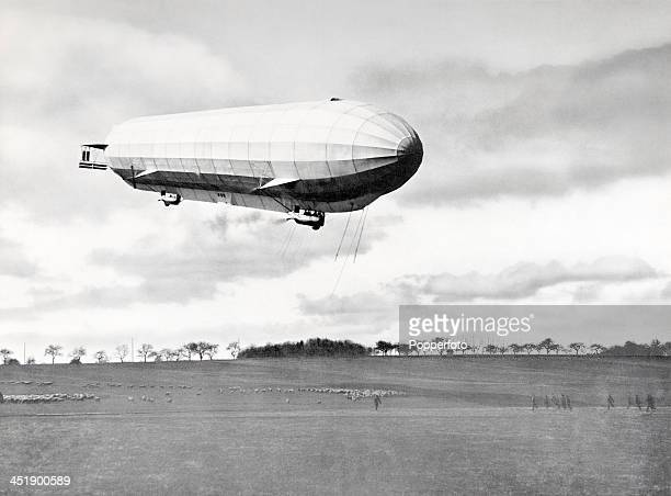 A zeppelin flying over fields and flocks of sheep circa 1920