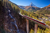 Image of Swiss Alps with Gornergrad tourist train, waterfall and Matterhorn in Valais region.