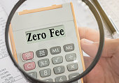 zero fee text displayed on calculator and magnifier. bank fees, service fee concept.