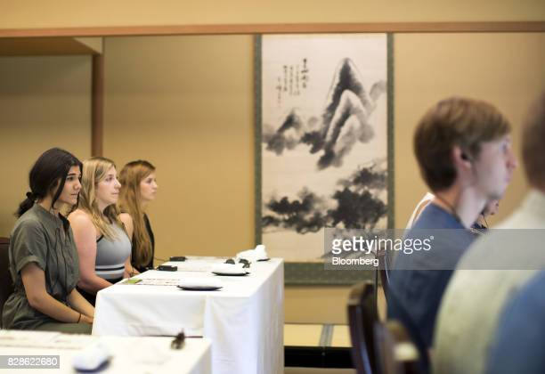 Zeynep Arican left listens to a Buddhist monk not pictured during a mindfulness lesson at a cultural experience program part of Mitsubishi UFJ...