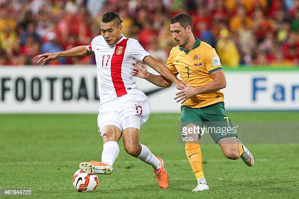 Zhang Chengdong of China is tackled by Mathew Leckie of Australia during the 2015 Asian Cup match between China PR and the Australian Socceroos at...