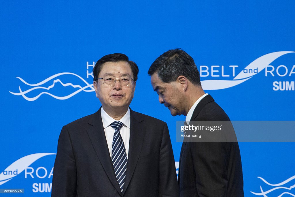 Zhang Dejiang, chairman of the Standing Committee of the National People's Congress, left, stands as Leung Chun-ying, Hong Kong's chief executive, walks on stage during the Belt and Road Summit in Hong Kong, China, on Wednesday, May 18, 2016. Hong Kong should take greater vision and keep an open mind to fully grasp the opportunities brought by President Xi Jinping's signature 'One Belt, One Road' initiative, Zhang said. Photographer: Justin Chin/Bloomberg via Getty Images