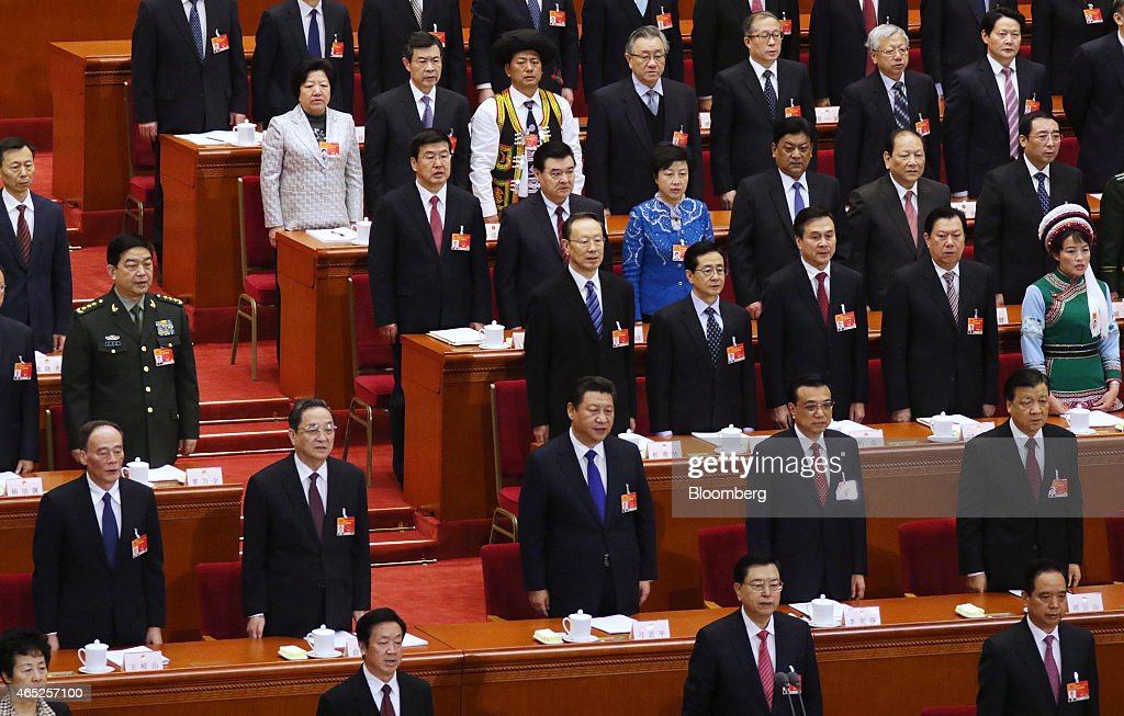 Zhang Dejiang, member of China's Politburo Standing Committee and chairman of the Standing Committee of the National People's Congress, front row second right, Wang Qishan, member of China's Politburo Standing Committee, second row from left, Yu Zhengsheng, member of China's Politburo Standing Committee, Xi Jinping, China's president, Li Keqiang, China's premier, and Liu Yunshan, member of China's Politburo Standing Committee, stand as they arrive for the opening of the third session of the 12th National People's Congress (NPC) at the Great Hall of the People in Beijing, China, on Thursday, March 5, 2015. China set the lowest economic growth target in more than 15 years and flagged increasing headwinds as leaders tackle the side effects of a generation-long expansion that spurred corruption, fueled debt and hurt the environment. Photographer: Tomohiro Ohsumi/Bloomberg via Getty Images