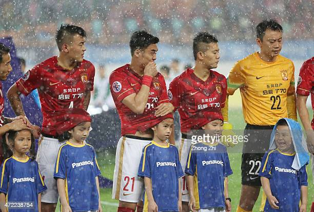 Zhang Jiaqi Zhao Xuri and Huang Bowen of Guangzhou Evergrande use their shirts to protect the ball kids during the heavy rain before the AFC Asian...