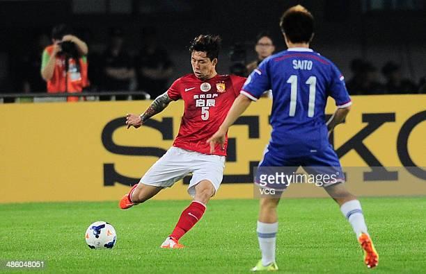 Zhang Linfan of Guangzhou Evergrande kicks a ball against Manabu Saito of Yokohama F Marinos during the AFC Asian Champions League match between the...