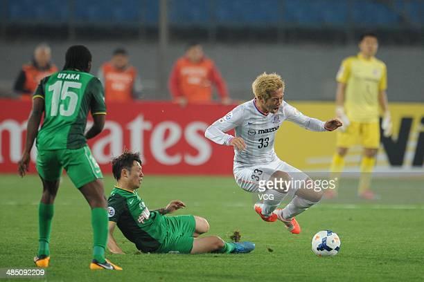 Zhang Xizhe of Beijing Guo'an and Tsukasa Shiotani of Sanfrecce Hiroshima battle for the ball during the Asian Champions League match between Beijing...