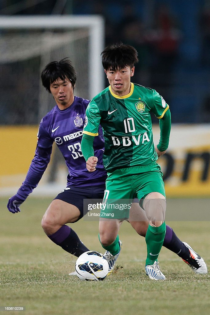 Zhang Xizhe (R) of Beijing Guo'an challenges Tsukasa Shiotani of Hiroshima Sanfrecce during the AFC Champions League Group match between Hiroshima Sanfrecce and Beijing Guoan at Beijing Workers' Stadium on March 13, 2013 in Beijing, China.