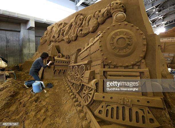 Zhang Yan of China finishes a sand sculpture named 'Siberian Railway and vladivostok as the Captial of far East' at the Sand Museum in the Tottori...