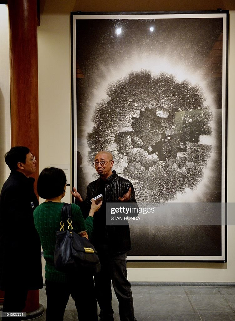 Zhang Yu (R) is interviewed in front of his piece, 'Divine Light Series No. 59, The Floating Incomplete Circle' on display in the exhibition 'Ink Art: Past as Present in Contemporary China' at the Metropolitan Museum of Art on December 9, 2013 in New York. A major exhibition of 70 pieces of art by 35 contemporary artists born in China goes on view to the public on December 11. AFP PHOTO/Stan HONDA ++RESTRICTED
