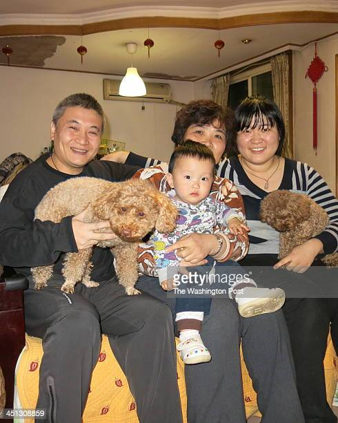 Zhang Yufei his son Zhang Enlang 13 months his motherinlaw Li Zhihong and his wife Ma Yanyan pose for a photograph in their family home in Beijing...