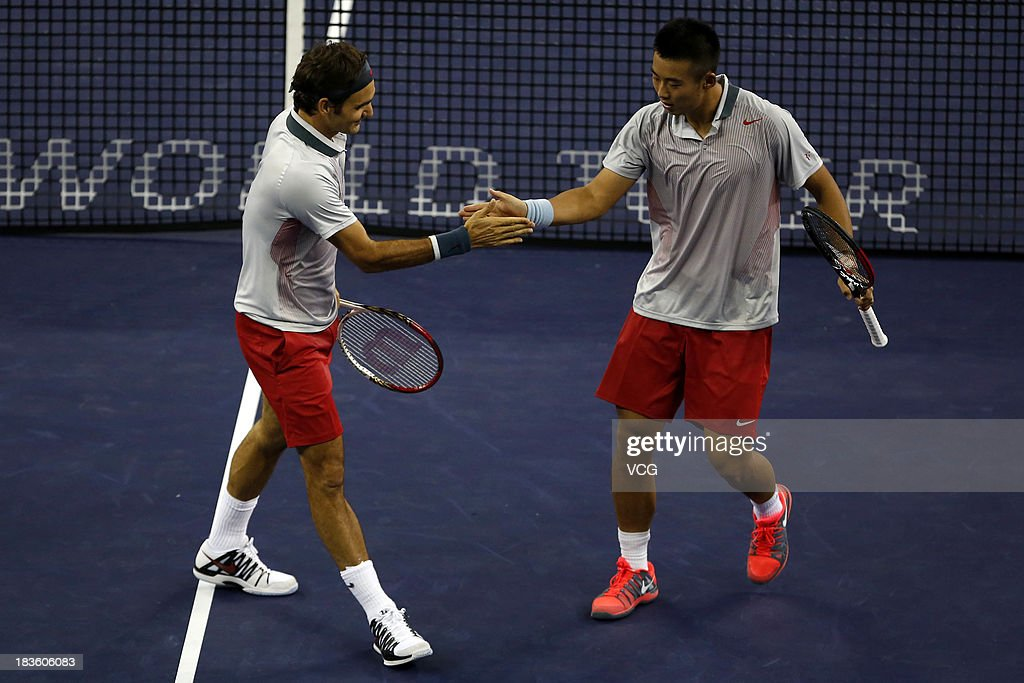 Zhang Ze (R) of China and Roger Federer of Switzerland in action during the men's first round doubles match against Kevin Anderson of South Africa and Dmitry Tursunov of Russia on day one of the Shanghai Rolex Masters at the Qi Zhong Tennis Center on October 7, 2013 in Shanghai, China.