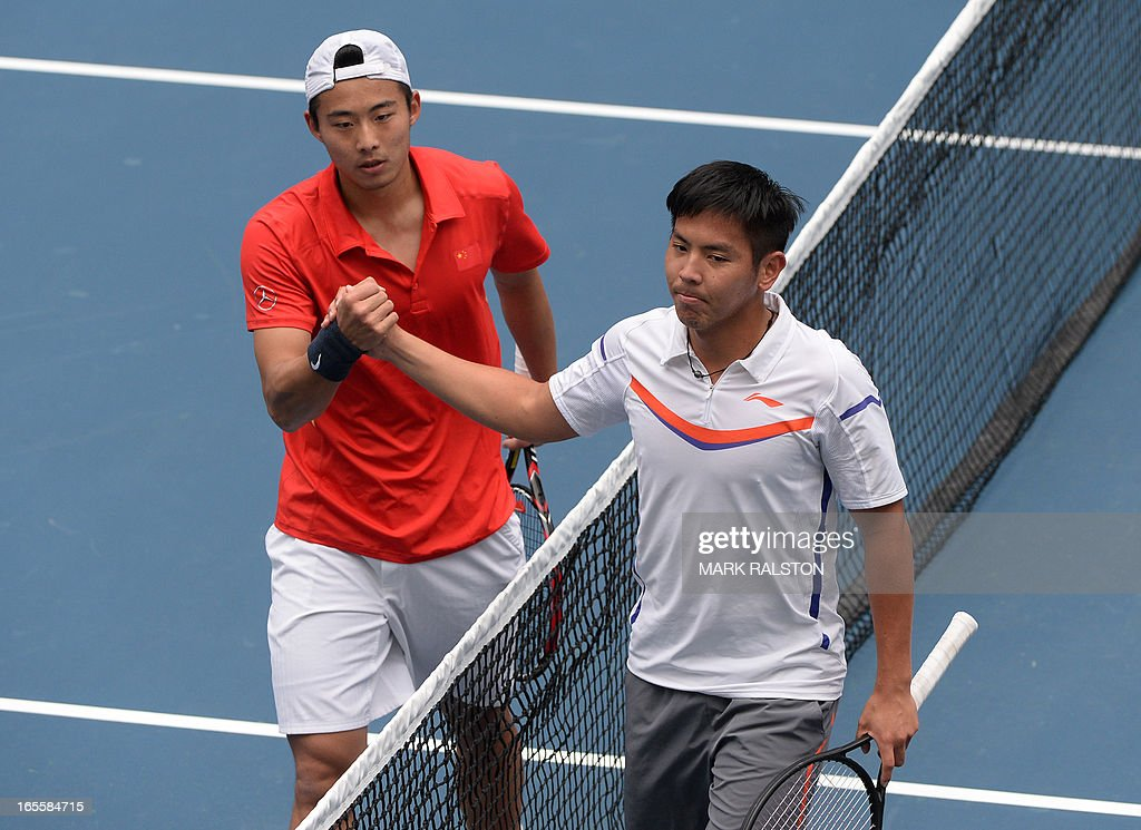 Zhang Ze of China (L) shakes hands with Yang Tsung-Hua of Taiwan (R) after winning their Davis Cup first round play-off match at the Tianjin Tennis Center on April 5, 2013. Zhang won 7-5, 6-1, 6-1 as China went 2-0 up in the event. AFP PHOTO/Mark RALSTON