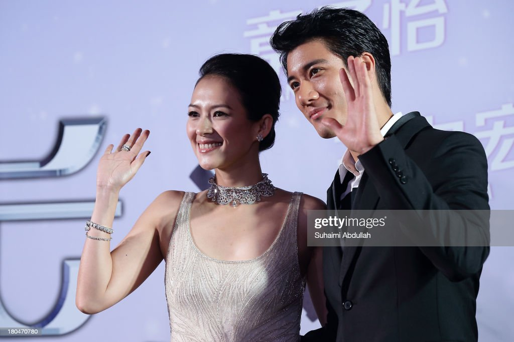 Zhang Ziyi and Wang Lee Hom wave to their fans during the red carpet event of the gala premiere of 'My Lucky Star' at The Shoppes at Marina Bay Sands on September 13, 2013 in Singapore.