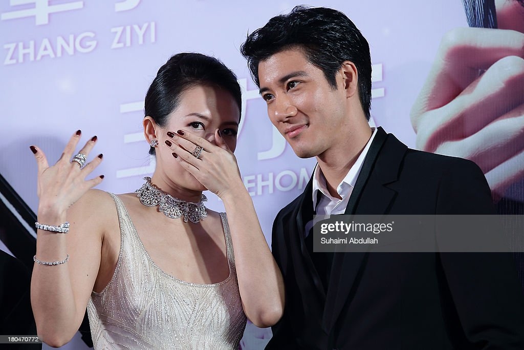 Zhang Ziyi (L) whispers to Wang Lee Hom during the red carpet event of the gala premiere of 'My Lucky Star' at The Shoppes at Marina Bay Sands on September 13, 2013 in Singapore.