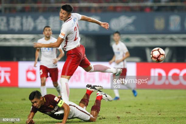 Zhao Mingjian of Hebei China Fortune fells to the ground and Yu Hai of Shanghai SIPG jumps up during the 21st round match of 2017 China Super League...
