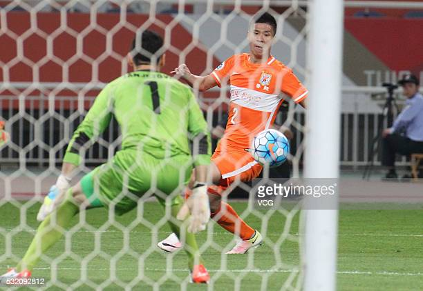 Zhao Mingjian of Shandong Luneng drives the ball in front of Goalkeeper Vedran Janjetovic of Sydney FC during the AFC Champions League Round of 16...