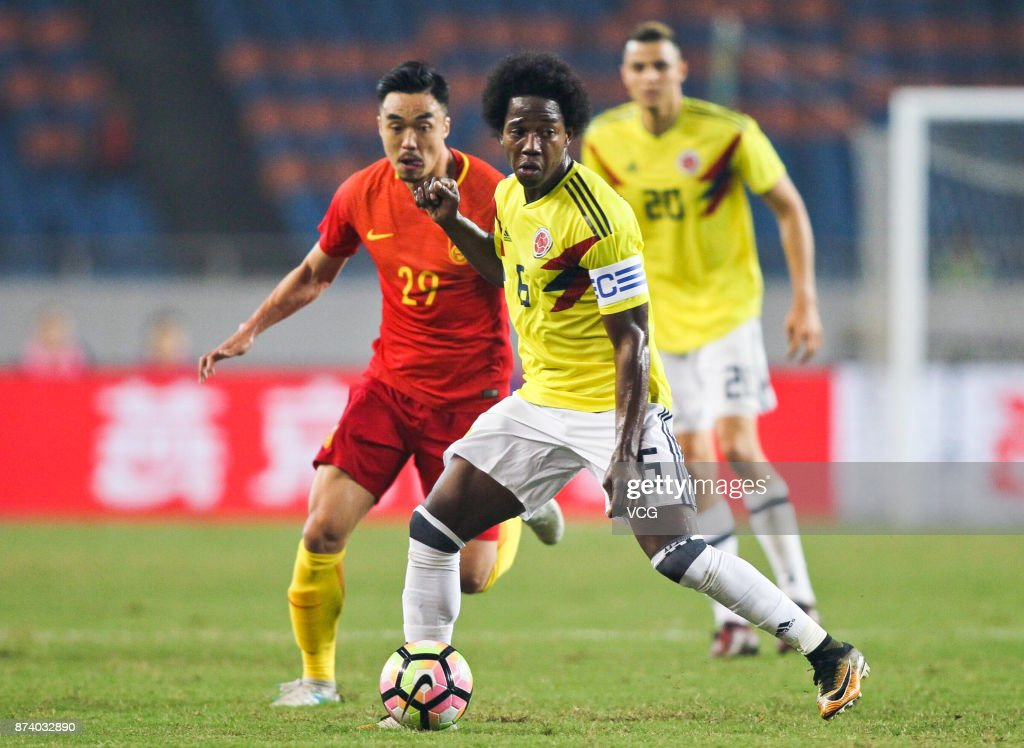 Zhao Xuri #29 of China National Team and Carlos Sanchez #6 of Columbia National Team compete for the ball during the international friendly match between China and Columbia at Chongqing Olympic Sports Centre on November 14, 2017 in Chongqing, China.