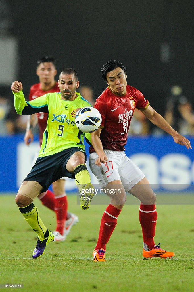 <a gi-track='captionPersonalityLinkClicked' href=/galleries/search?phrase=Zhao+Xuri&family=editorial&specificpeople=596391 ng-click='$event.stopPropagation()'>Zhao Xuri</a> #37 of Guangzhou Evergrande and Sergio Escudero #9 of FC Seoul battle for the ball during the AFC Champions League Final 2nd leg match between Guangzhou Evergrande and FC Seoul at Tianhe Sports Center on November 9, 2013 in Guangzhou, China.