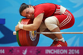 Zhazira Zhapparkul of Kazakhstan celebrates by hugging her successfully lifted weight in the Women's 75kg Weightlifting Final during day six of the...