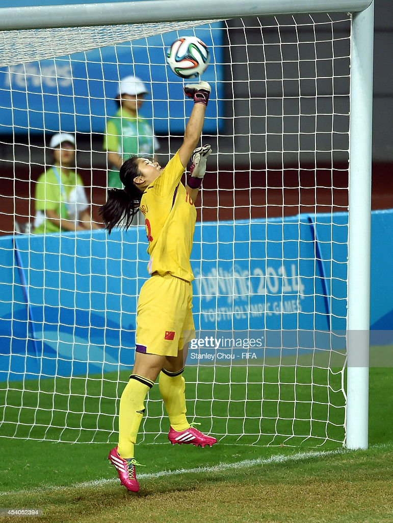 Zheng Jie of China saves a penalty in the penalty shoot out after the full time scorelss draw during the 2014 FIFA Girls Summer Youth Olympic Football Tournament Semi Final match between China and Slovakia at Wutaishan Stadium on August 23, 2014 in Nanjing, China.