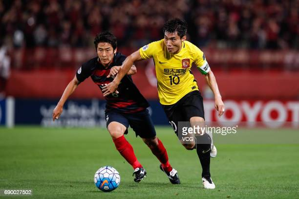 Zheng Zhi of Guangzhou Evergrande and Ryota Nagaki of Kashima Antlers vie for the ball during the AFC Champions League Round of 16 match between...