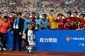 Zhi Zhang of Guangzhou Guangzhou lifts up the Volkswagen Cup Guangzhou winners trophy after the international friendly match between FC Guangzhou...