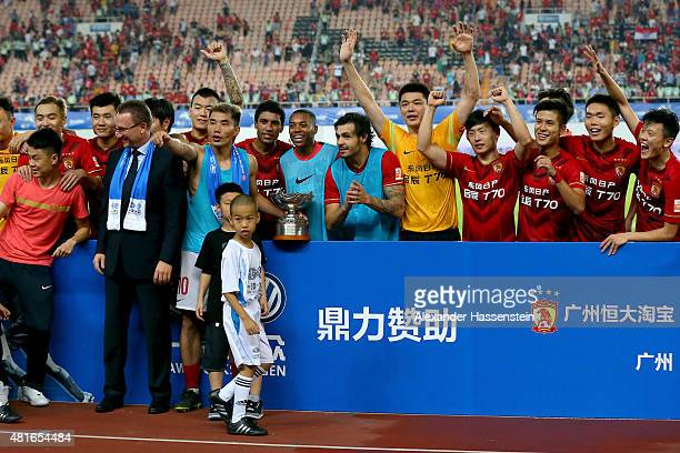 Zhi Zhang of Guangzhou Guangzhou lifts up the Volkswagen Cup Guangzhou winners trophy after the international friendly match between FC Guangzhou...