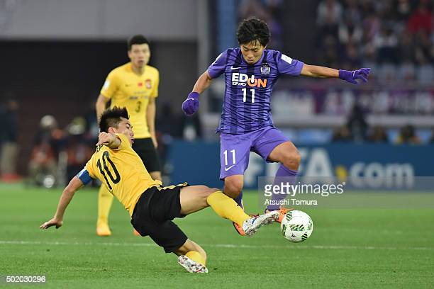 Zhi Zheng of Guangzhou Evergrande FC and Hisato Sato of Sanfrecce Hiroshima compete for the ball during the 3rd place match between Sanfrecce...