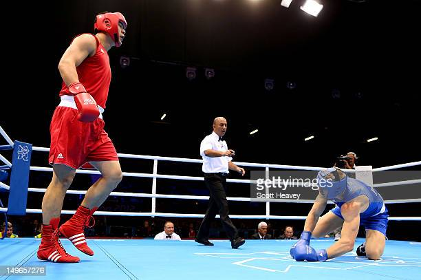 Zhilei Zhang of China knocks down Johan Linde of Australia during the Men's Super Heavy Boxing on Day 5 of the London 2012 Olympic Games at ExCeL on...