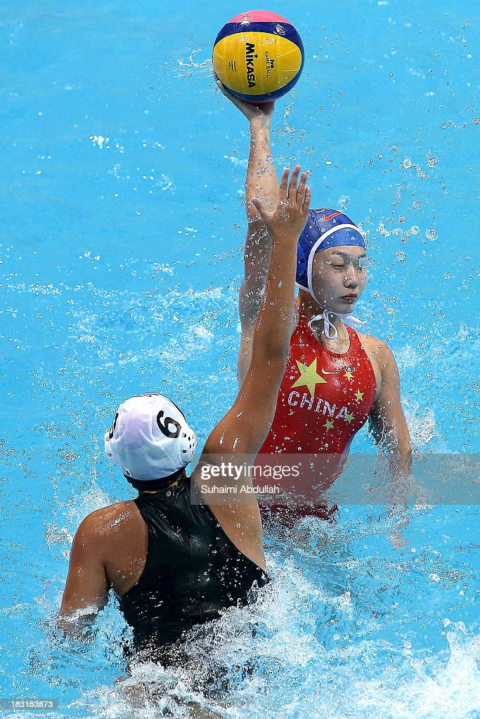 Zhong Chong (R) of China looks for a pass against Kornkarn Puengponsakul (L) of Thailand during the women Asian Water Polo Cup between Thailand and China at Toa Payoh Swimming Complex on October 5, 2013 in Singapore.