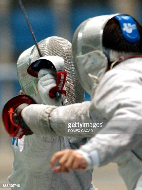 Zhou Hannming of China and Kim Doo Hong of South Korea duel during the fencing men's sabre team final at the 14th Asian Games in Busan 04 October...
