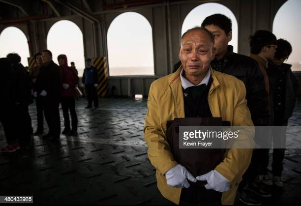 Zhou Ming Fa 72 years fights back tears as he waits to deposit the ashes of his late wife Bai Ping Lan into a metal chute during a sea burial...
