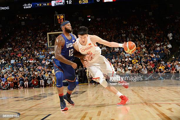 Zhou Qi of China handles the ball against DeMarcus Cousins of the USA Basketball Men's National Team on July 26 2016 at ORACLE Arena in Oakland...