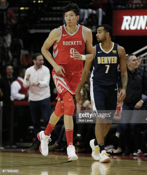 Zhou Qi of the Houston Rockets shoots a three point shot over Trey Lyles of the Denver Nuggets at Toyota Center on November 22 2017 in Houston Texas...
