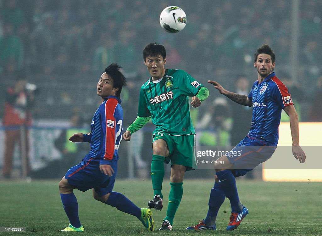 Zhou Ting of Beijing Guoan challenges Mario Bozic and Cao Yunding of Shanghai Shenhua during the Chinese Super League match at Workers Stadium on...
