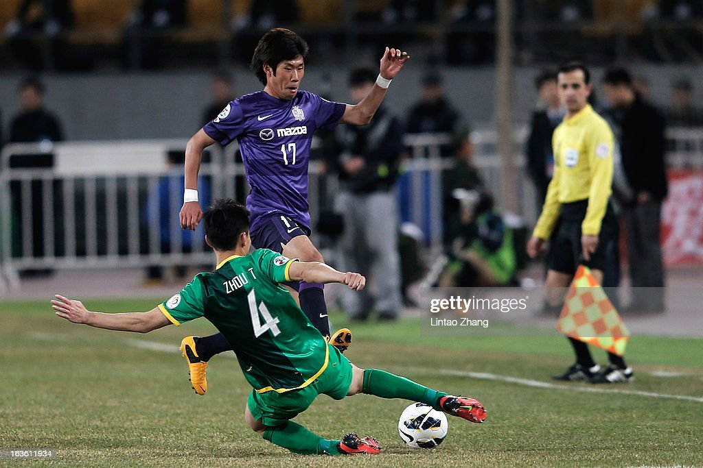 Zhou Ting (#4 ) of Beijing Guo'an challenges Park Hyung-Jin of Hiroshima Sanfrecce during the AFC Champions League Group match between Hiroshima Sanfrecce and Beijing Guoan at Beijing Workers' Stadium on March 13, 2013 in Beijing, China.