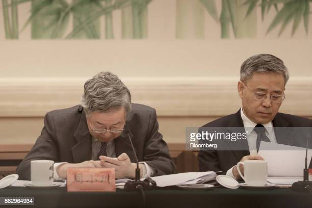 Zhou Xiaochuan governor of the People's Bank of China left looks at his smart phone as Guo Shuqing chairman of the China Banking Regulatory...