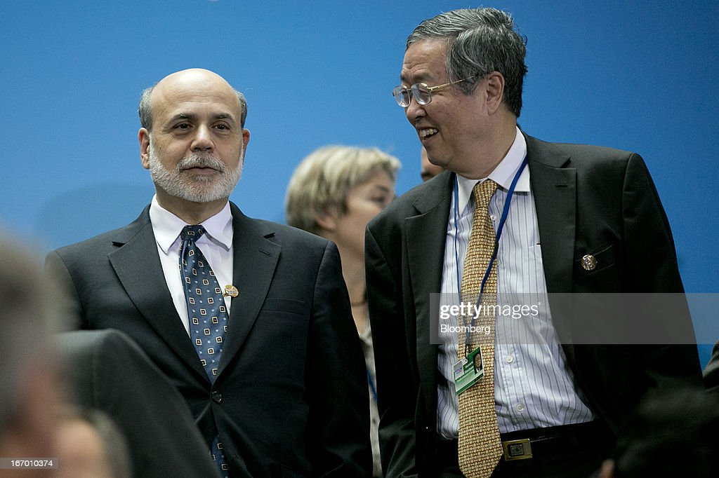 Zhou Xiaochuan, governor of the People's Bank of China, right, talks to Ben S. Bernanke, chairman of the U.S. Federal Reserve, during a Group of 20 nations (G- 20) finance ministers and central bank governors family photograph on the sidelines of the International Monetary Fund (IMF) and World Bank Group Spring Meetings in Washington, D.C., U.S., on Friday, April 19, 2013. The G-20 economies reaffirmed a commitment to move more rapidly to market-determined currencies, while avoiding 'persistent exchange-rate misalignments.' Photographer: Andrew Harrer/Bloomberg via Getty Images