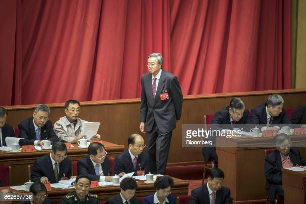 Zhou Xiaochuan governor of the People's Bank of China walks past other delegates during the opening of the 19th National Congress of the Communist...