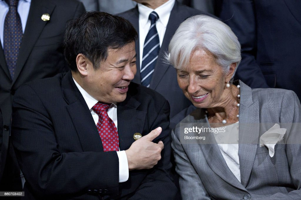 Zhu Guangyao, China's vice minister of finance, left, talks to Christine Lagarde, managing director of the International Monetary Fund (IMF), during a Group of 20 (G-20) finance ministers and central bank governors group photo on the sidelines of the International Monetary Fund (IMF) and World Bank Group Annual Meetings in Washington, D.C., U.S., on Thursday, Oct. 12, 2017. Near-term risks to world financial stability have declined since April amid improving macroeconomic conditions and the subsiding risk of emerging-market turmoil, the IMF said in its latest Global Financial Stability Report released yesterday. Photographer: Andrew Harrer/Bloomberg via Getty Images