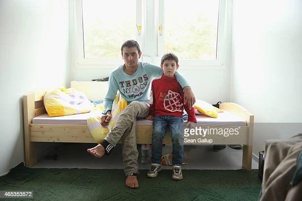 Zia from Afghanistan and his neighbour Mustafa from Palestine pose for a photo in the room Zia shares with his cousin at the container settlement for...