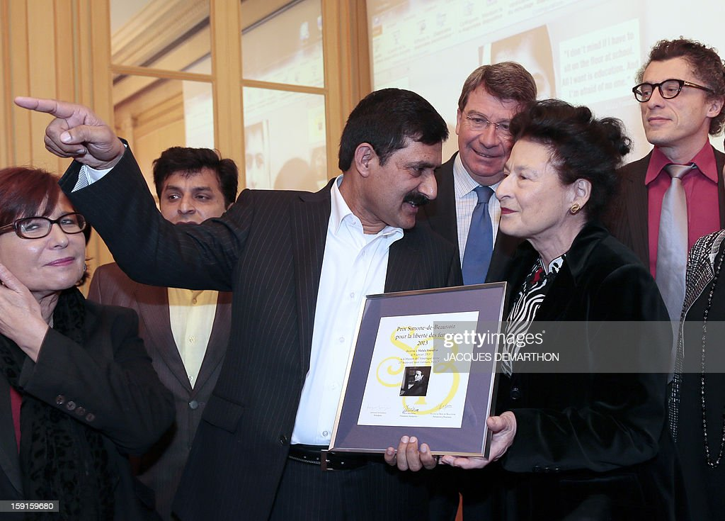 Ziauddin Yousafzai (C), the father of Malala Yousafzai, the young Pakistani schoolgirl activist who was the victim of an assasination attempt by the Taliban in 2012, receives the 2013 Simone de Beauvoir award from the hands of Sylvie Le Bon de Beauvoir (R) during the awards ceremony in Paris on January 9, 2013. The 2013 Simone de Beauvoir prize for the freedom of women was handed to Malala Yousafzai, who has become a symbol of the struggle for girls' education and women's rights in Pakistan. Malala was flown to the United Kingdom with a life-threatening head wound shortly after her attack but recovered from her injuries and was temporarily discharged on January 4 as she awaits more surgery.